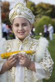 Turkey, Istanbul, Sultanahmet, Young boy eating sweetcorn cooked on the cob, wearing traditional Turkish ceremonial attire standing in front of the Blue Mosque on the day of his circumcision.