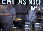England, East Sussex, Brighton, People serving themselves vegetarian curry in the Bombay Alloo Eat as Much as you Like Indian restaurant in Ship Street.
