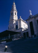 Portugal, Beira Litoral, Fatima, Woman in large hat sat at the bottom of the steps in front of the church.