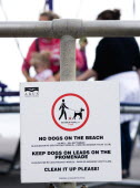 England, West Sussex, Bognor Regis, Sign on seafront railings warning that no dogs are allowed on the beach, must wear leads on the promenade and must be cleaned up afterwards.