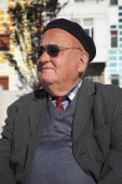 Albania, Tirane, Tirana, Head and shoulders portrait of an elderly man wearing beret and sunglasses. Three-quarter profile left.