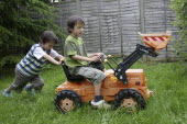 Children, Playing, Outdoor, Two twin boys playing outside on a toy tractor.