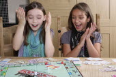 Children, Playing, Indoor, board games, two young girls playing Monopoly.