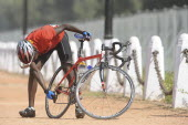 India, Delhi, 2010 Commonwealth games, Road cycling event competitor checking gears on his bike.