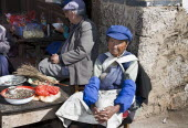 China, Yuunan, Baisha, Old Naxi woman wearing traditional costume, selling goods on market stall in the village near Lijiang.