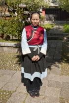 China, Yunnan Province, Baisha, Young Naxi woman wearing traditional costume.