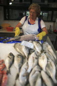 Portugal, Lisbon, A vendor descales a fish at her stall in the Ribeira market.
