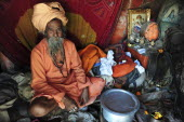 India, Uttarakhand, Hardiwar, Portrait of Saddhu sitting inside makeshift tent surrounded by belongings during Kumbh Mela,  Indias biggest religious festival where many different traditions of Hinduis...