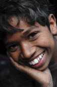 India, Uttarakhand, Hardiwar, Close cropped portrait of smiling young boy with head resting on his hand.