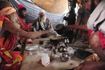 India, Uttarakhand, Hardiwar, Saddhus preparing meal over open fire inside tent during Kumbh Mela, Indias biggest religious festival.