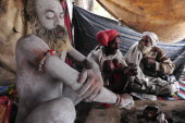 India, Uttarakhand, Hardiwar, Saddhu Baba Gajender Girri Marraj covering his body with ash inside tented area during Kumbh Mela, Indias biggest religious festival.