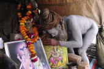 India, Uttarakhand, Hardiwar, Saddhu Baba Gajender Girri Marraj with his body covered in ash beside shrine of statue  images and offerings inside tent during Kumbh Mela festival.