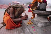 India, Uttarakhand, Hardiwar, Saddhu praying at shrine draped with flower garland offerings during Kumbh Mela, Indias biggest religious festival where many different traditions of Hinduism come togeth...