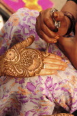 India, Uttarakhand, Hardiwar, Cropped shot of woman applying henna paste in decorative pattern to the palm of the hand of another.