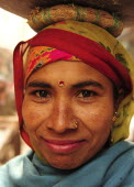 India, Uttarakhand, Hardiwar, Head and shoulders portrait of smiling young woman carrying vessel on her head.