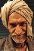 India, Uttarakhand, Hardiwar, Head and shoulders portrait of man wearing turban of brown cloth.