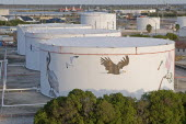 USA, Florida, Tampa, An attempt to put an environment friendly face on oil storage tanks along Maritime Boulevard.