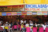 Mexico, Bajio, Zacatecas,  Feria food stalls with customers eating on tables outside.