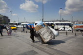 Turkey, Istanbul, Eminonu, man transporting rubbish by handcart across the square outside the NEw mosque.