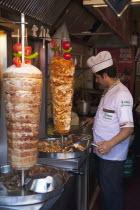 Turkey, Istanbul, Sultanahmet, man in kebab restaurant carving shawarma from skewered meats.