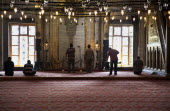 Turkey, Istanbul, Sultanahmet Camii, Blue Mosque interior with men at worship.