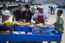 Turkey, Istanbul, Karakoy, Galata fish market, man selling freshly grilled fish served in a bread roll.