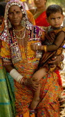 India, Karnataka, Lambani Gypsy woman holding child. Tribal forest dwellers, now settled in 30-home rural hamlets. Related to the Rabaris gypsies of Kutch, Gujarat.