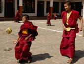 India, Sikkim, Buddhist student monks playing soccer at a monastery.