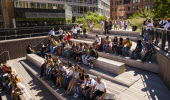 USA, New York, Manhattan, West Side, High Line Park, 10th Ave Square, Theater area with high school students sat waiting for performance.