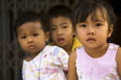 Thailand, Bangkok, Young children in late afternoon sun in front of shophouse entrance.