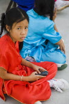 Thailand, Bangkok, Thai girls using mobile telephone in costume of dance troupe.