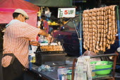Thailand, Bangkok, Street vendor selling sausages in early evening light, 5 Baht each, cheapest food in the city.