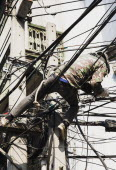 Thailand; Bangkok; Chinatown, Workman, in camouflage, repairing overhead cables in hot afternoon sun.