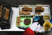 Thailand, Bangkok, Primary School girl in uniform at sausage stall outside BTS Skytrain station.