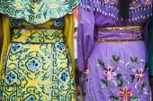 Thailand, Bangkok, Embroidered womens dresses viewed from behind.