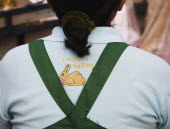 Thailand, Bangkok, Thai woman wears shirt with Long live the King embroidery, and Rabbit for year 2011, a symbol of peace.