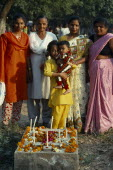 India, Delhi, All Souls Day in Christian cemetary, family group around grave decorated with flowers and candles.