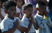 Thailand, Chiang Mai, Buddhist Schoolchildren with hands held in prayer, one child yawning.