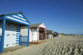 England, West Sussex, West Wittering Beach, Colourful beach huts along sandy beach.