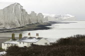 England, East Sussex, Seven Sisters, Snow covered chalk cliffs viewed from the coastguard cottages at Cuckmere Haven.