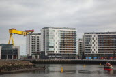 Ireland, North, Belfast, Titanic Quarter, Modern apartment blocks on the site of the Harland & Wolff shipyard with sightseeing cruise boat.