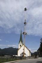 Austria, Tyrol, Brandenberg, Malbaum or Maypole outside village church.