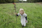 Kids, Outdoor, 5 year old Eva with stick & leaf flag in a field of grass.