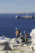 France, Brittany, Gulf of Brest, Climbers preparing to scale Pointe de Penhir.