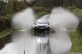 Weather, Floods, Flooded country road with cars driving slowly through waters.