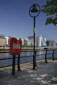 Ireland, County Dublin, Dublin City, river Liffey with the Convention Centre, streetlamp and lifebuoy in foreground.