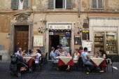 Italy, Lazio, Rome, Diners eating al fresco at a restaurant in a back street.