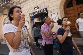 Italy, Lazio, Rome, Eating ice cream outside a Gelateria in a back street.