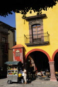 Mexico, Bajio, San Miguel de Allende, El Jardin, Part view of yellow painted facade of colonial mansion with French window and balcony, with fruit juice vendor in street below.