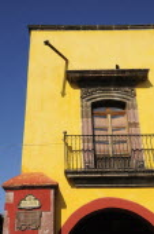 Mexico, Bajio, San Miguel de Allende, El Jardin, Part view of yellow painted exterior facade of building with French windows and balcony.